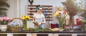 Cheerful beautiful young woman florist in glasses smiling and working in flower shop